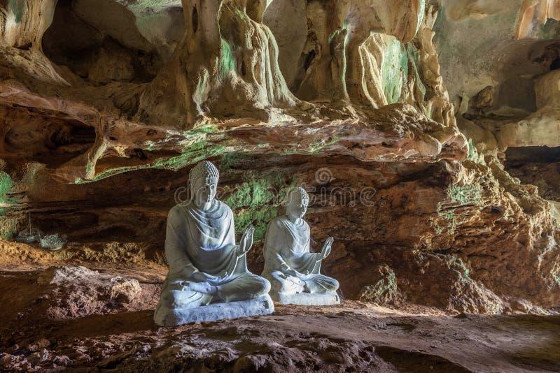 Vita statyer av Buddha i grotta arkivfoton