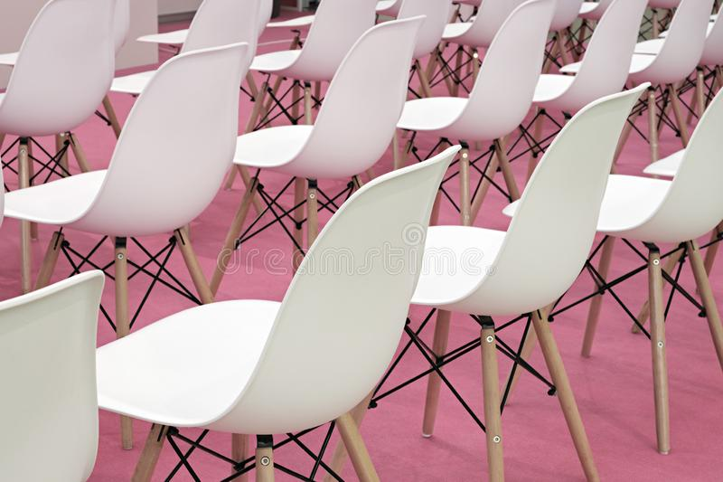 Vita stolar för konferens i affärsrum, rader av vita plast- bekväma platser i tomt företags kontor för presentationsmöte, royaltyfri foto