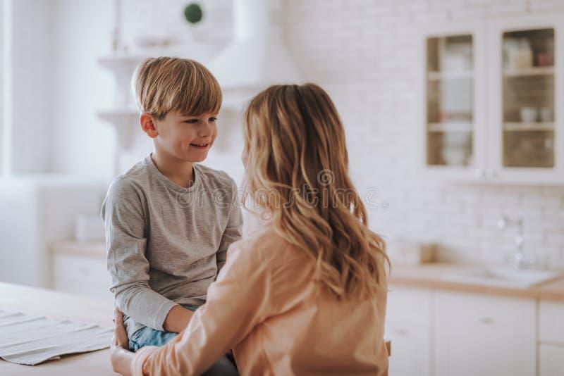 Vita su del ragazzo allegro che sorride a sua madre nella cucina immagine stock libera da diritti