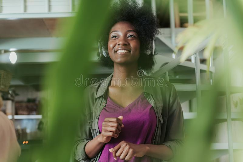 Vita su delle cuffie d'uso della donna africana felice e di situazione sulle scale fotografia stock libera da diritti
