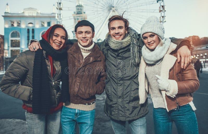 Vita su di quattro giovani amici che stanno in vestiti caldi all'aperto fotografia stock