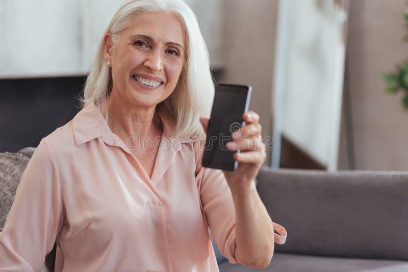 Vita su di una donna invecchiata allegra che mostra il suo nuovo smartphone fotografie stock