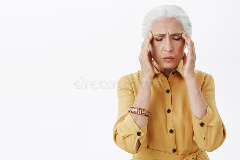 Vita-su sparata della donna anziana esaurita interessata in trench giallo alla moda che si tiene per mano sulle tempie con chiuso fotografia stock libera da diritti
