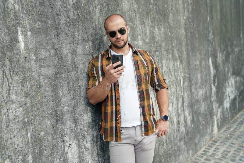 Vita sul ritratto di giovane bello tipo barbuto audace che sta all'aperto contro la parete moderna grigia del sottotetto con il t fotografie stock