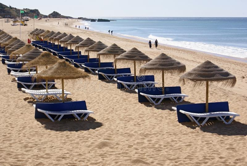 Vita sunbeds med blå matting med traditionella bastslags solskydd på en sandig strand arkivfoton