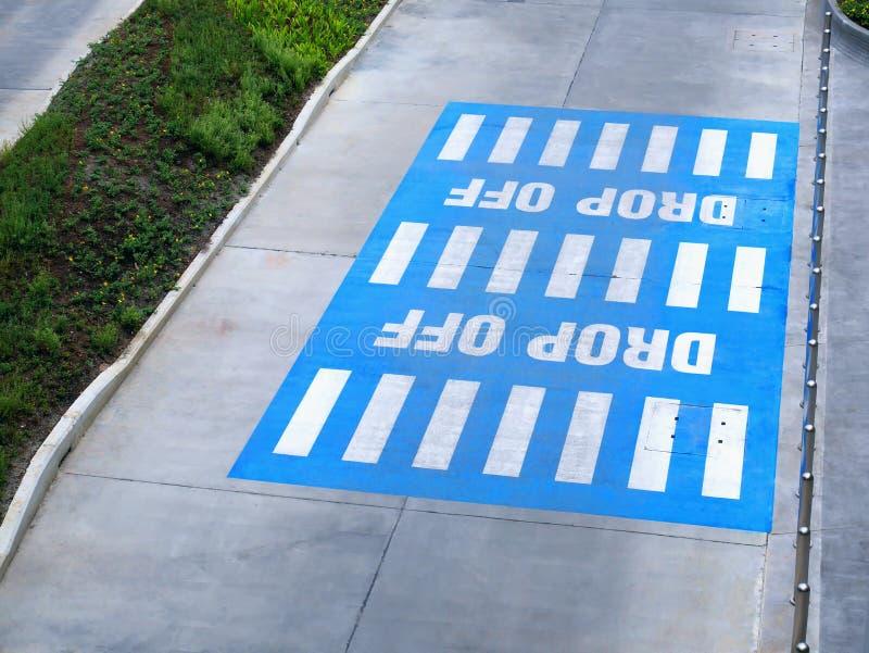 Vita texter för droppe målade av på blått rektangulärt område på gatan arkivfoton