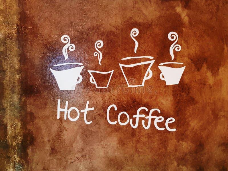 Vita texter och symboler av varmt kaffe på den Grungy bruna väggen royaltyfri foto