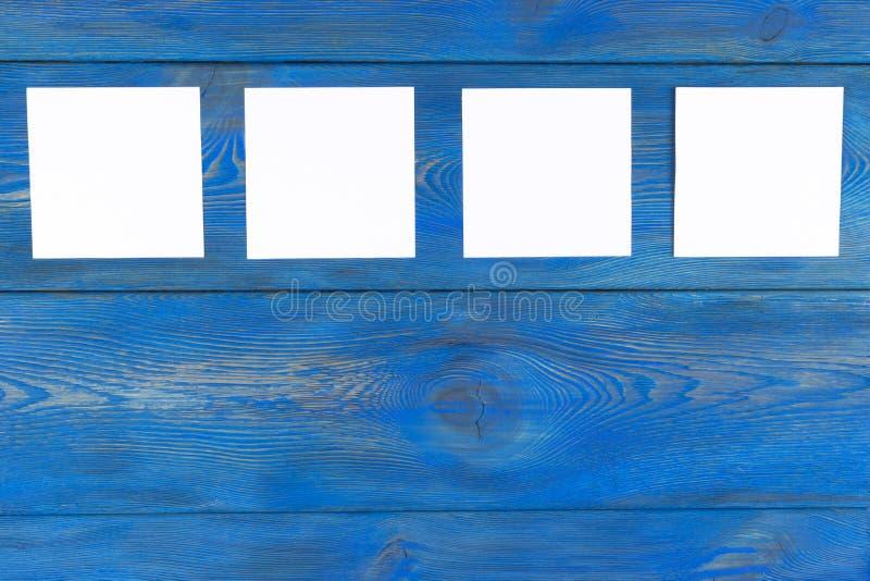 Vita tomma kort på den blåa trätabellen med kopieringsutrymme Idérik påminnelse, små ark av papper på skrivbordet med tomt utrymm arkivbilder