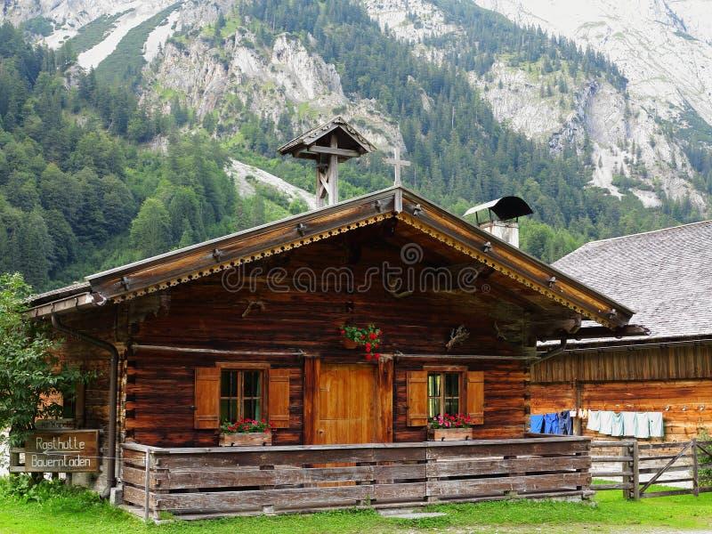 Vita tradizionale del cottage di legno in montagne immagini stock