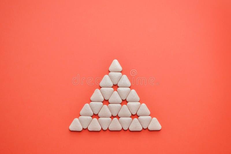 Vita triangulära ovanliga minnestavlor läggas i formen av en triangel på en korallbakgrund med copyspace arkivfoton