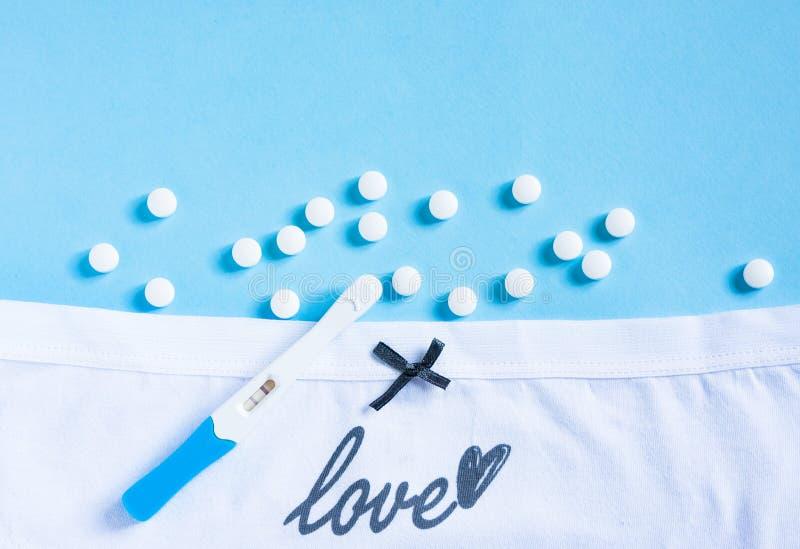 Vita trosor av honkön med bog, p-piller och graviditetstest på blå bakgrund Hälso- och sjukvård, preventivmedel och planerade arkivbilder