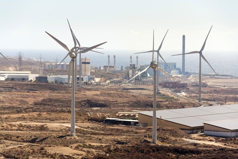 Vita turbiner på vindlantgården med kraftverket och havet i bakgrund, ointressant landskap på solig sommardag arkivbilder
