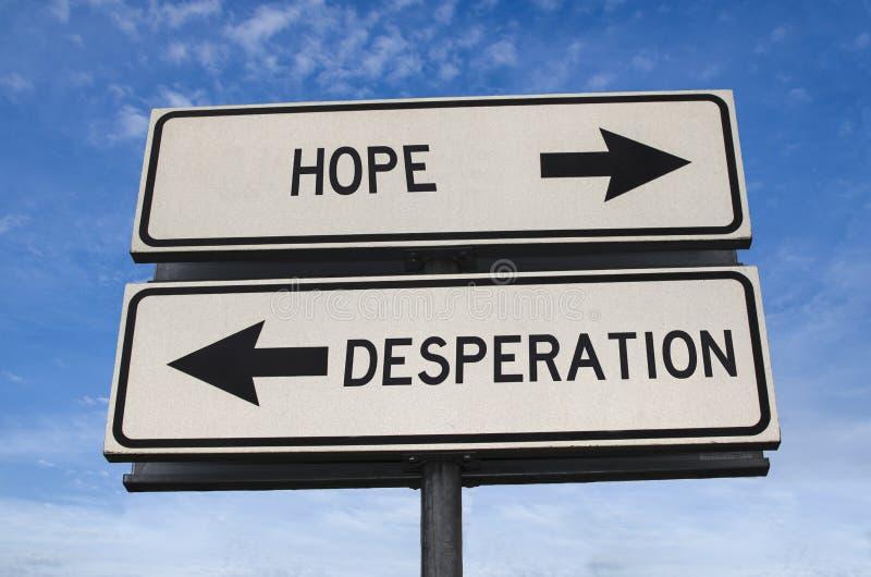 Vita två gatuskyltar med pil på metallpolen med ord och hopp och desperation arkivfoton