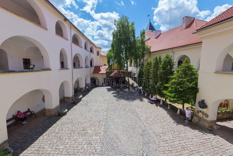 Vita väggar med bågar av borggården av Mukacheven rockerar Turister undersöker brunnen royaltyfri bild
