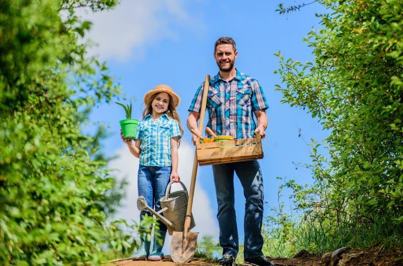 Vita verde uomo dell'agricoltore con la bambina strumenti, pala e annaffiatoio di giardino Lavoratore del bambino con la scatola  fotografia stock