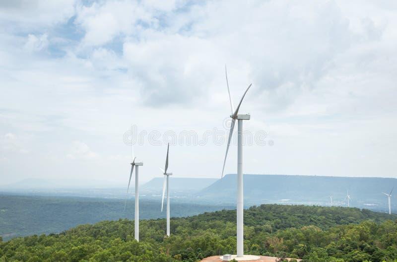 Vita vindturbiner som frambringar elektricitet i vindkraftstation arkivbilder