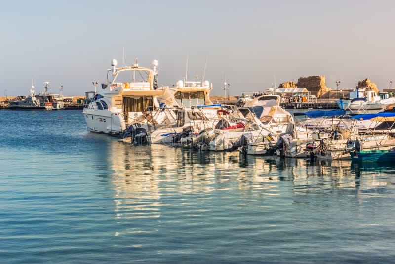 Vita yachter och fartyg på pir i porten av Paphos i strålarna av solnedgången arkivfoton