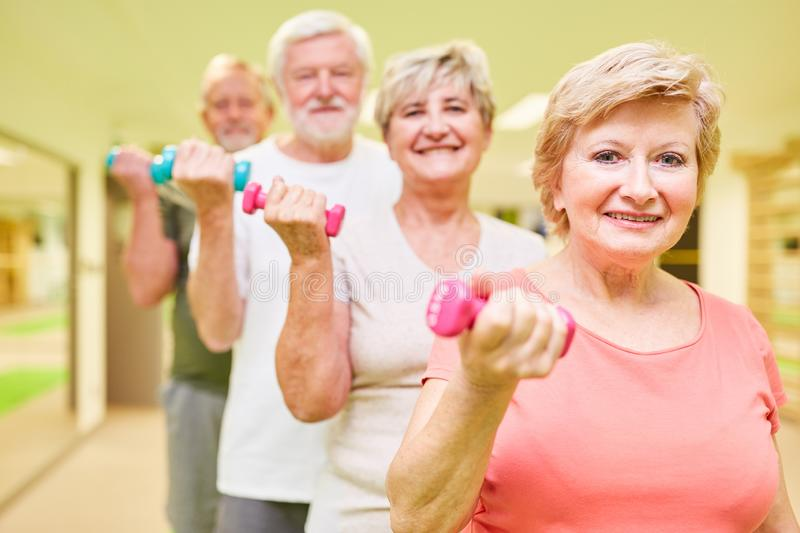 Vital seniors group trains with dumbbells. Vital seniors group trained with dumbbells in the fitness center for muscle growth and strength stock photography