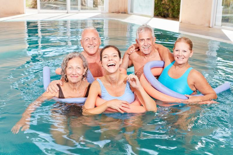 Vital group of seniors in the swimming pool. Vitale group seniors in the swimming pool is doing water aerobics rehab course royalty free stock photo