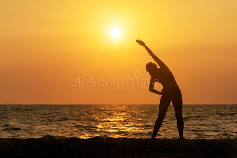 Vitalidade da paz da mulher da mente do estilo de vida do espírito do exercício, ar livre da silhueta no nascer do sol do mar, imagem de stock