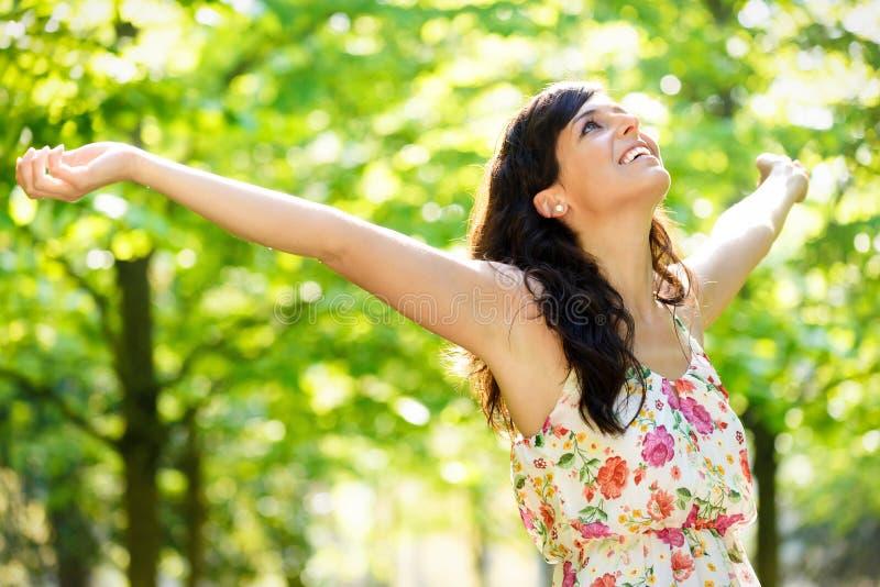 Vitalità felice della donna sul parco della molla fotografia stock