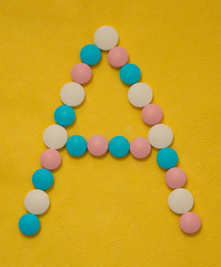 Vitamin A. Letter A composed of tablets, vitamins different colors stock photos