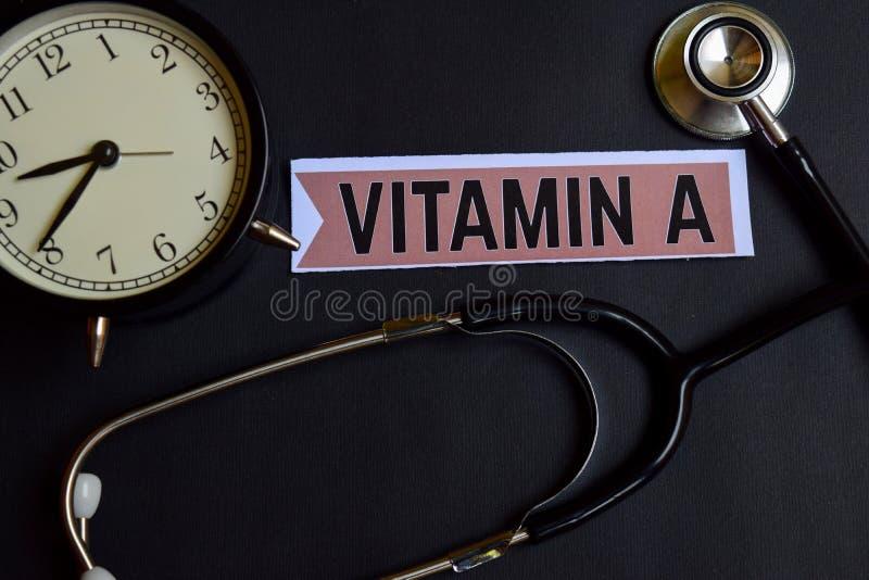 Vitamin A auf dem Papier mit Gesundheitswesen-Konzept-Inspiration Wecker, schwarzes Stethoskop lizenzfreie stockbilder