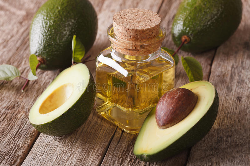 Vitamin avocado oil in a glass bottle on a table close-up, horiz royalty free stock photo