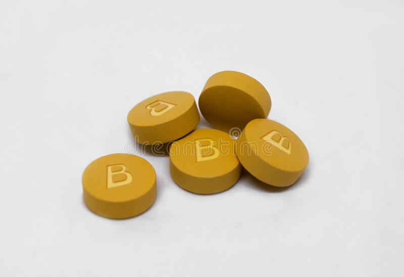Vitamin B pills isolated on a white background. Vitamin B pills to create energy and red blood cells with text isolated on a white background stock photos