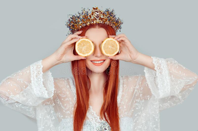 Vitamin C and beauty. A young woman holding covering eyes with two slices of orange lemons as a eye area skin mask pretty woman royalty free stock photography