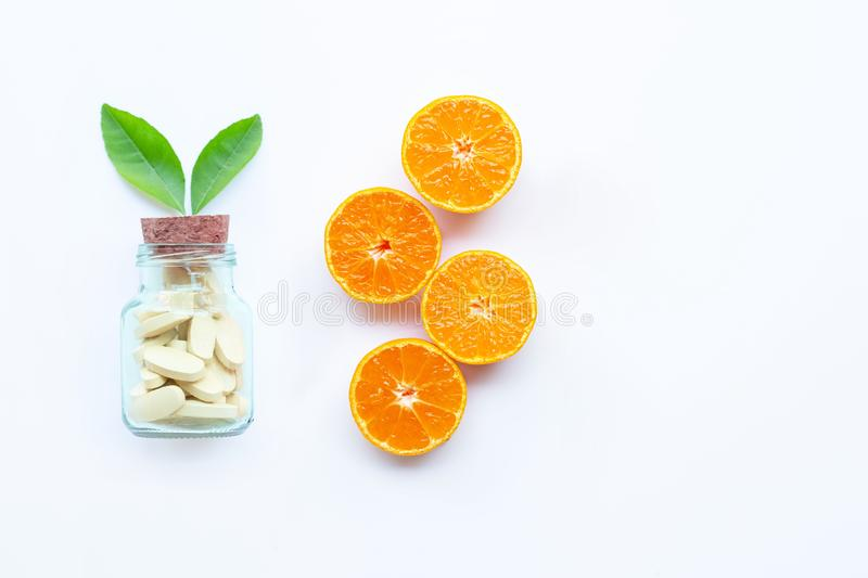 Vitamin C bottle and pills with orange fruit on white royalty free stock images