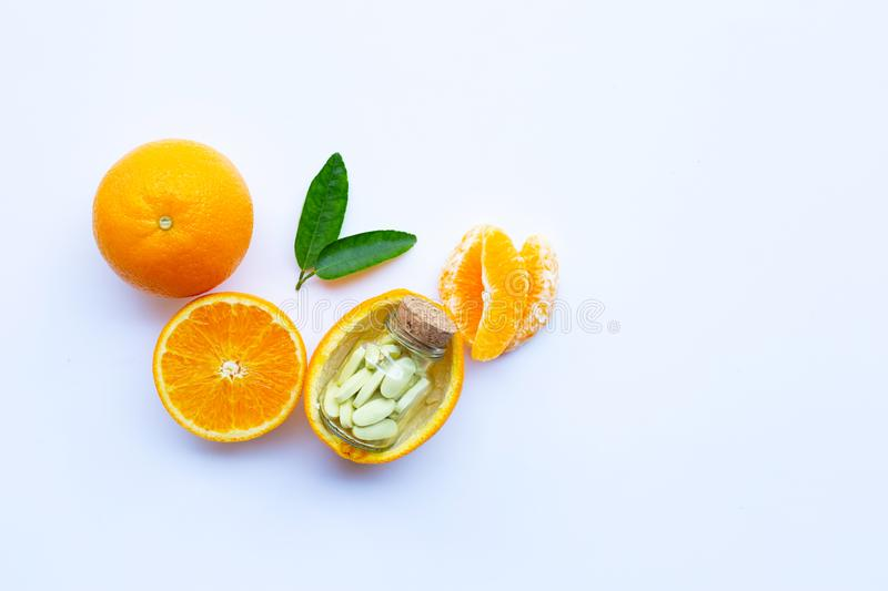 Vitamin C bottle and pills with orange fruit on white background stock photography