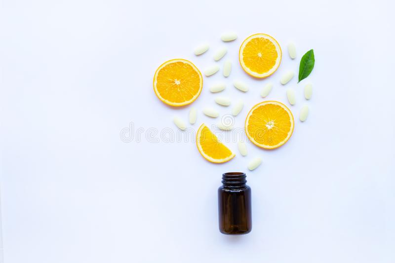 Vitamin C bottle and pills with orange fruit on white stock photography