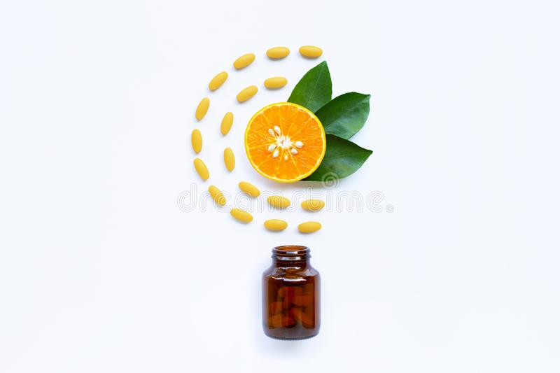 Vitamin C bottle and pills with orange fruit on white royalty free stock photography