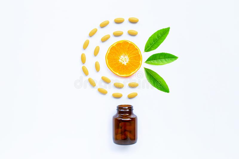 Vitamin C bottle and pills with orange fruit on white royalty free stock image