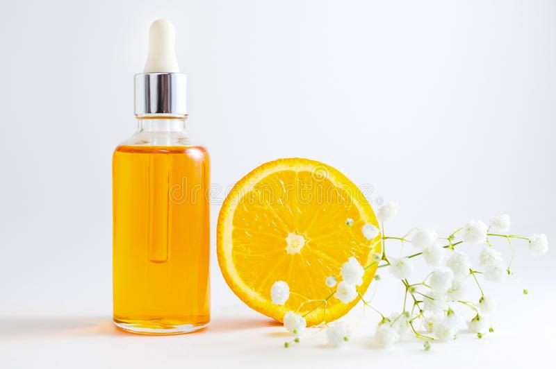 Vitamin C serum in cosmetic bottle with dropper, sliced orange and flowers on white background. Organic SPA cosmetics with herbal. Cosmetic bottle with dropper stock images