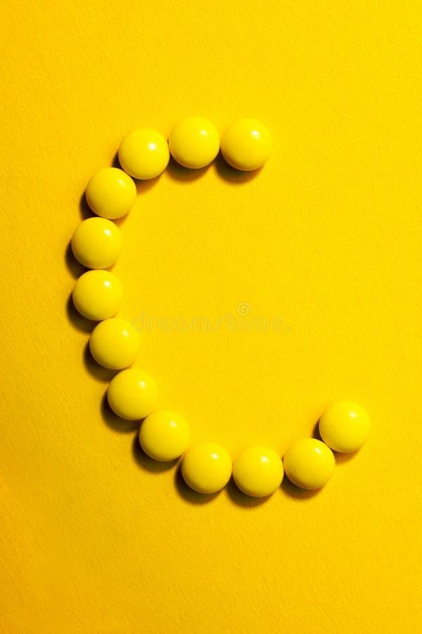 Vitamin- Cpillen-Buchstabe lizenzfreie stockfotografie
