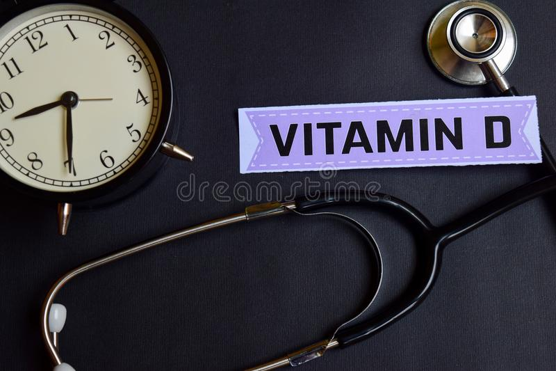Vitamin D on the paper with Healthcare Concept Inspiration. alarm clock, Black stethoscope. stock image