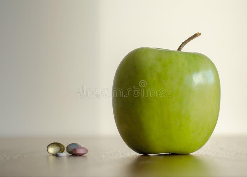 Vitamin in den Pillen gegen großen grünen Apfel Konzept des Gesundheit benef lizenzfreie stockfotos