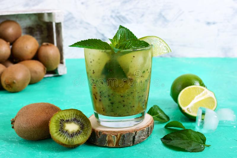 Vitamin drink with kiwi, mint, lime, soda in a glass on a bright background. Summer refreshing beverage royalty free stock images