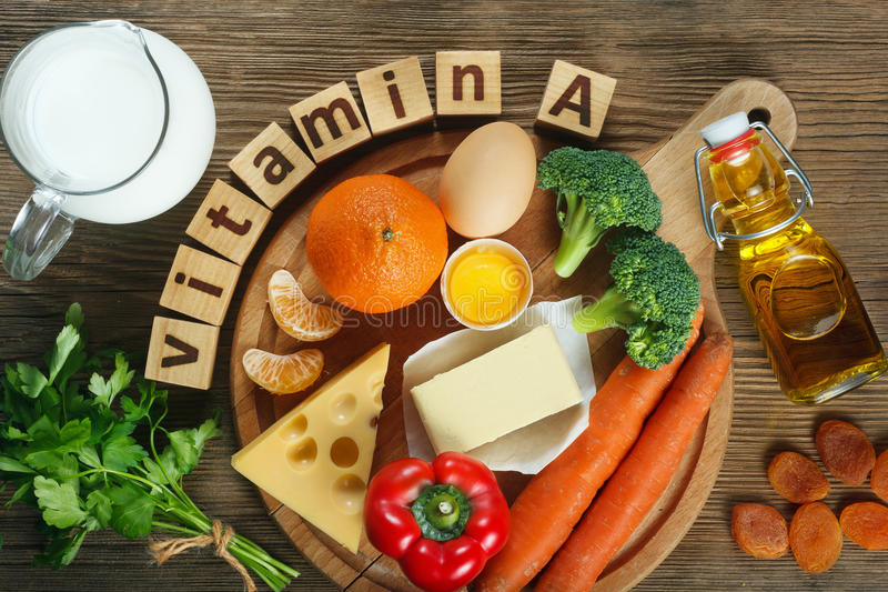 Vitamin A in food. Natural products rich in vitamin A as tangerine, red pepper, parsley leaves, dried apricots, carrots, broccoli, butter, yellow cheese, milk stock image