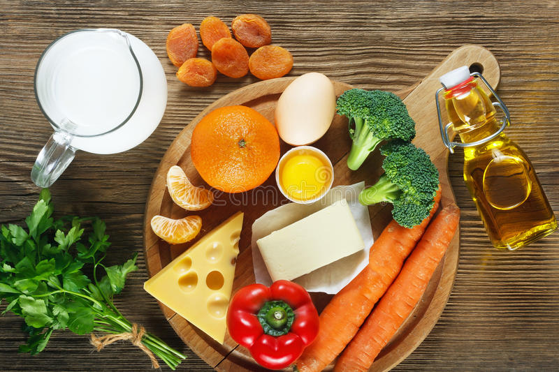 Vitamin A in food. Natural products rich in vitamin A as tangerine, red pepper, parsley leaves, dried apricots, carrots, broccoli, butter, yellow cheese, milk stock images