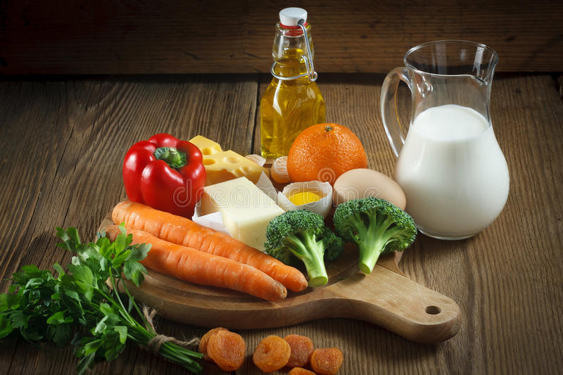 Vitamin A in food. Natural products rich in vitamin A as tangerine, red pepper, parsley leaves, dried apricots, carrots, broccoli, butter, yellow cheese, milk stock photo