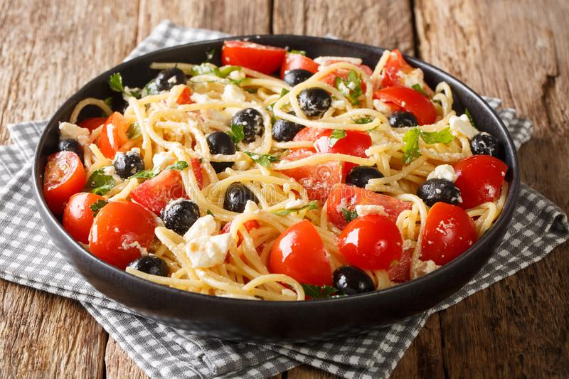 Vitamin fresh greek pasta spaghetti salad with cheese and vegetables close-up on a plate. horizontal stock photo