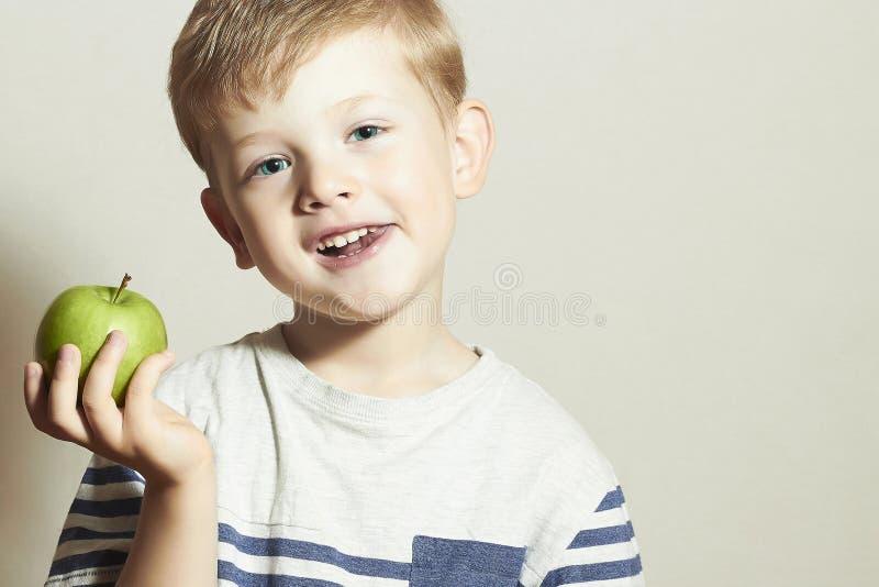 vitamin Le barnet med äpplet Little Boy med det gröna äpplet white för studio för makro för hälsa för mat för bakgrundshavreflake arkivbilder