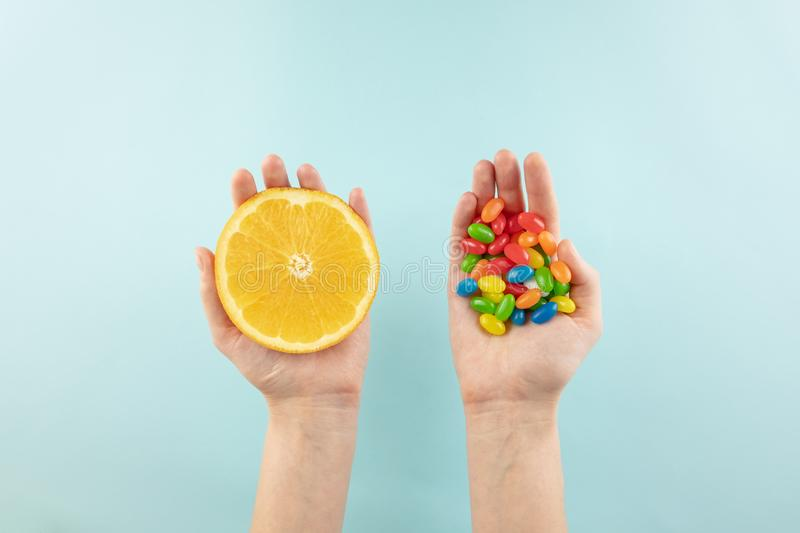 Vitamin pills and fresh orange in hands, top view. stock image