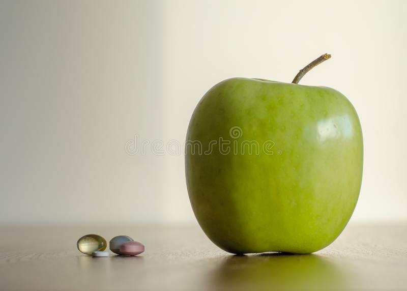 Vitamin in pills vs big green apple. concept of the health benef royalty free stock photos