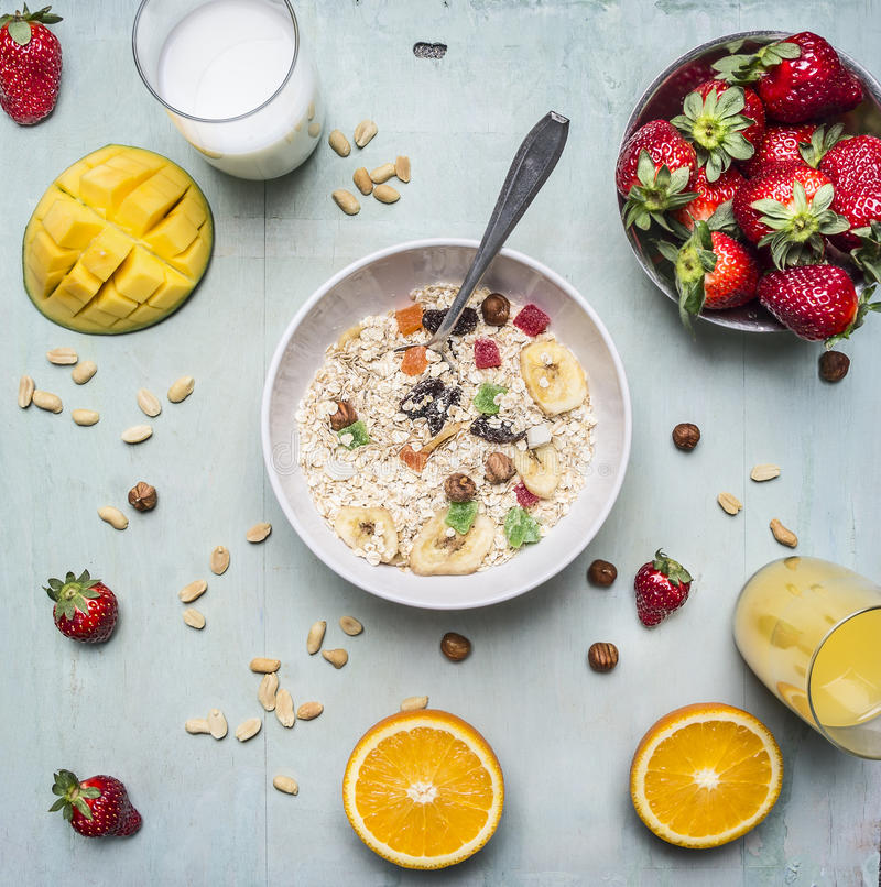 Vitamin-rich breakfast, oatmeal with nuts and dried fruits, strawberries and mango, fresh juice on wooden rustic background top vi royalty free stock photography