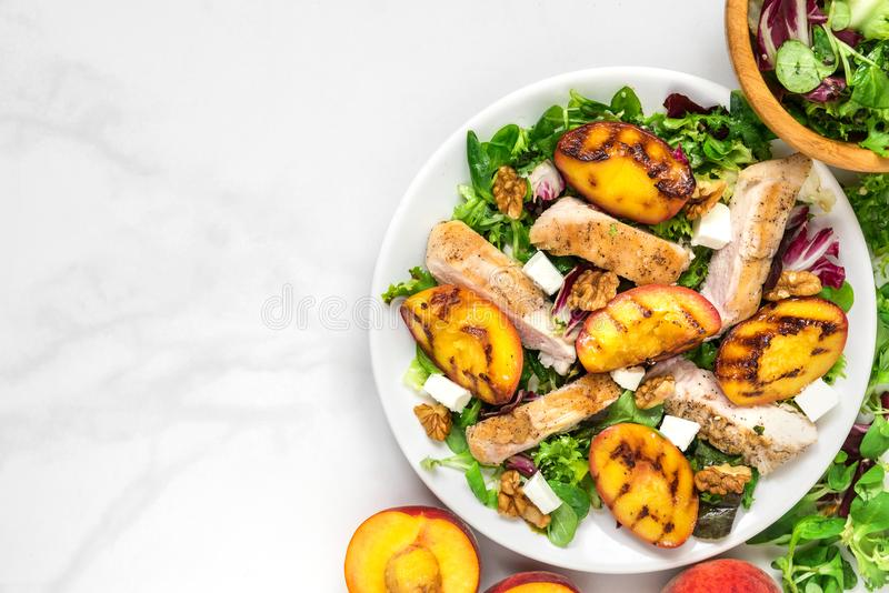 Vitamin salad with grilled chicken and peach, feta cheese and walnuts in a plate. healthy food. top view. With copy space stock photography