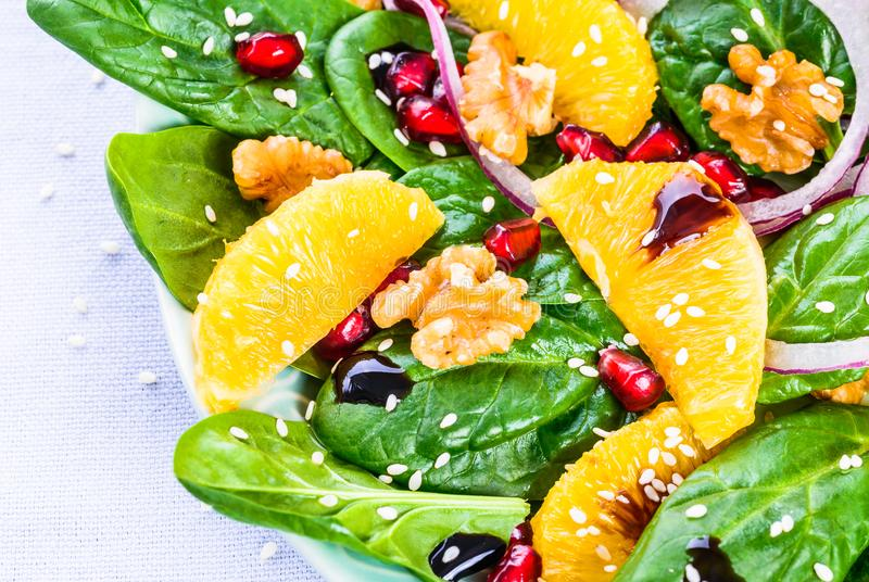 Vitamin salad plate with fresh spinach leaves and orange. royalty free stock photography